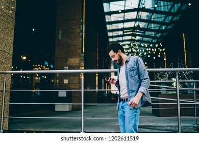 Side view of casual dressed hipster guy strolling in urban setting near business building and reading received notification on smartphone.Young man chatting in social networks on cellular on street