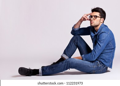 side view of a casual fashion man sitting on gray background and looking away from the camera