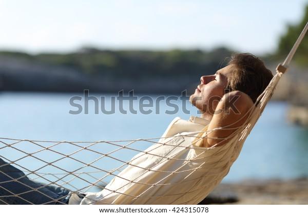 Seitenansicht eines glücklichen Mannes, der sich im Urlaub auf einer Hängematte am Strand entspannt