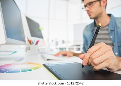 Side view of a casual male photo editor using graphics tablet in a bright office