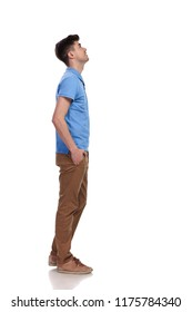 side view of a casual man with hands in pockets looking up at something on white background