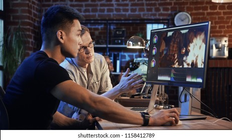 Side view of casual man and producer working on computer and editing video with color correction of documentary or commercial video