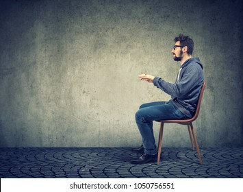 Side view of casual man sitting at invisible table pretending to type on computer.