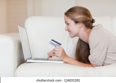 Side view of casual woman doing online shopping through laptop and credit card