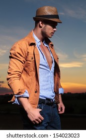 side view of a casual young man standing outdoor with a straw in his mouth and a thumb in his pocket while looking away from the camera with the sunset behind him