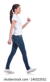 side view of a casual young woman walking away from the camera and smiling. isolated on white background