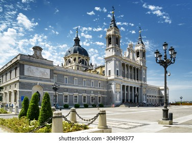Side view of the Cathedral of Saint Mary the Royal of La Almudena on the blue sky background with white clouds in Madrid, Spain. Madrid is a popular tourist destination of Europe.