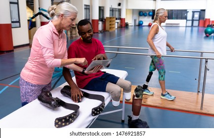 Side view of Caucasian active senior female trainer and disabled African-american man discussing over digital tablet in sports center. Sports Rehab Centre with physiotherapists and patients working