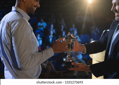 Side view of Caucasian businessman giving trophy to mixed race business male executive on stage in auditorium