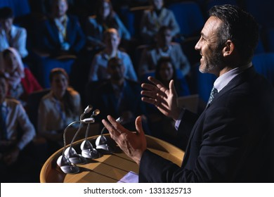 Vista lateral del empresario caucásico de pie y dando una presentación en el auditorio