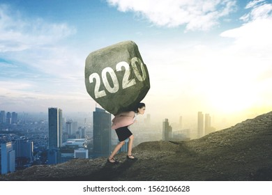 Side view of Caucasian businesswoman carrying numbers 2020 in a rock while climbing on a cliff