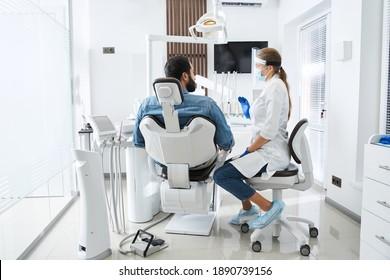 Seitenansicht der kaukasischen Zahnärztin, die mit ihrem Patienten spricht und ihn auf die Behandlung vorbereitet. Schwerer bärtiger Mann im Zahnarztstuhl, der den Arzt ansieht und etwas verlangt