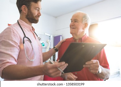 Side view of a Caucasian male doctor showing medical report to Caucasian senior patient in clinic