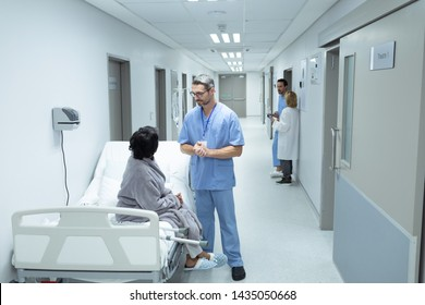 Side view of Caucasian male doctor interacting with disabled female patient in the corridor at hospital