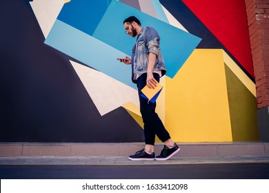 Side view of Caucasian male student with education textbooks walking near colorful wall and using 4g wireless internet for mobile messaging, millennial blogger networking publication content