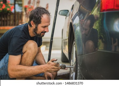 Side view of a caucasian man unscrewing a modern  car wheel with a ratchet. Service of a car, changing tyres or wheels at home.