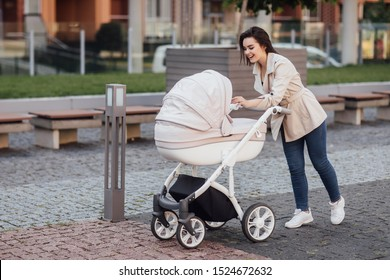 Side view of a Caucasian Mum walking on city street while pushing her toddler sitting in a pram. Family concept.