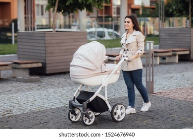 Side view of a Caucasian Mum walking on city street while pushing her toddler sitting in a pram.