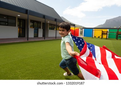 Side view of a Caucasian schoolboy running with an American flag in the school playground on a sunny day