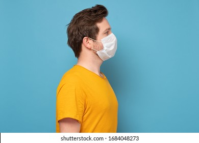 Side view of caucasian young man with single use medical mask to prevent infection, respiratory disease such as flu, 2019-nCoV. indoor studio shot isolated