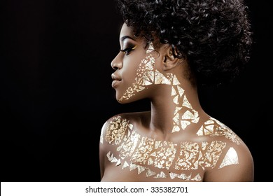 Side view of charming african girl, with black curly hair and patterns of golden foil on her skin, posing on the black background, in studio, close up