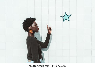 Side view of a charming young African woman in sunglasses wagging her finger at a painted star above her head as a symbol of an idea that came to mind; a black girl is pointing up with her forefinger
