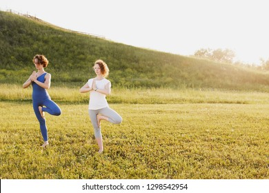 Side view of a charming young slim girls with curly hair and doing vrikshasana on a green lawn in a sunny summer park on the background of a hill. Concept of health and longevity
