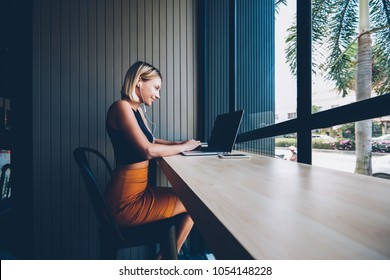 Side view of cheerful blonde young womam listening music in modern earphones from website while doing shopping online on laptop computer connected to wireless 4G internet resting in coffee shop
