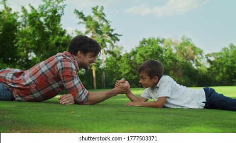 Side view cheerful boy and man armwrestling on green grass in meadow. Closeup father and son practising arm wrestling together outdoors. Happy boy winning competition in armwrestling at summer park