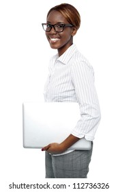 Side view of cheerful business consultant carrying laptop isolated against white background