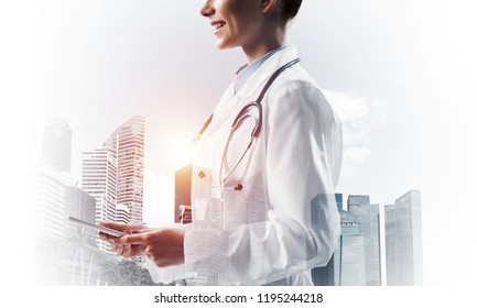 Side view of cheerful female doctor in sterile suit holding tablet in hands and smiling while standing against cityscape view on background. Medical industry. Double exposure