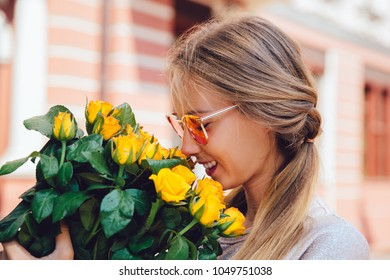 Side view of cheerful gorgeous woman in sunglasses, sniffs yellow roses, outside. Summertime
