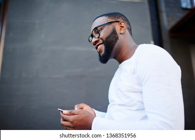 Side view of cheerful male blogger in optical eyewear for vision correction looking away while waiting for email from friend, happy smiling hipster guy with cellphone enjoying time on publicity area