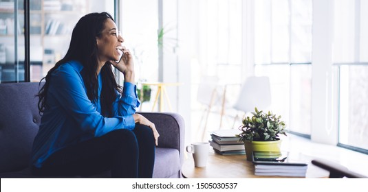 Side view of cheerful young African American woman sitting on couch in light room having phone call at home looking away