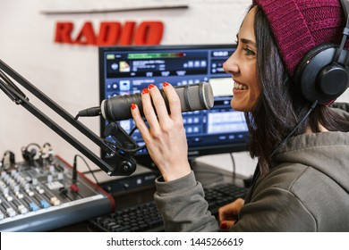 Side view of a cheerful young woman radio host broadcasting through microphone in studio