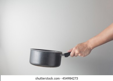 Side view of chef hand holding a cooking pot preparing food. Cooking action concept