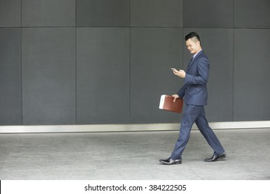 Side view of a Chinese businessman walking outdoors and using his Smart phone in modern Asian city. Business on the go concept.