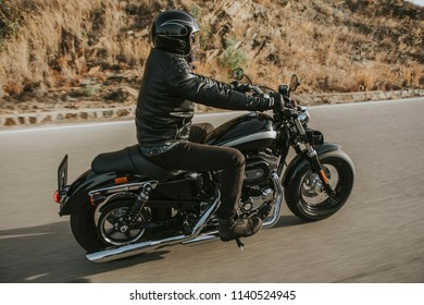 Side view of classic motorbike rider riding an American classic motorcycle