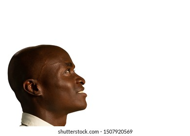 Side view close up of a bald young African American businessman wearing a shirt and tie, looking up and smiling