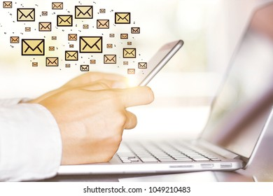 Side view and close up of businessman hands using smartphone and laptop with email sketch. E-mail marketing concept