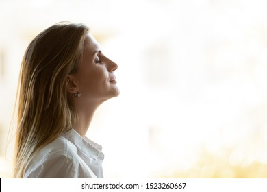 Side view close up head shot young mindful businesswoman breathing fresh air, managing stress at office. Calm peaceful millennial female manager, company owner or team leader meditating at workplace.