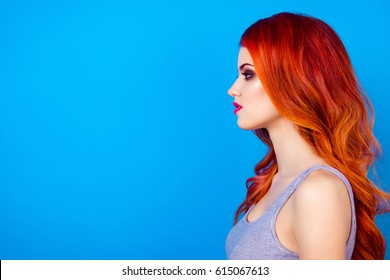 Side view close up photo of attractive pretty girl with long ginger fair hair standing on blue background