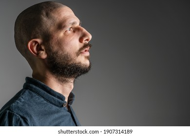 Side view close up portrait of adult caucasian man with beard and short hair looking up thoughtful with copy space - studio shot