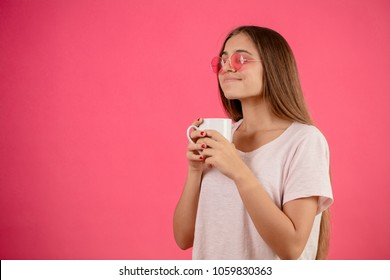 side view close up portrait of funny model with closed eyes wearing sunglasses enjoying hot coffee. sip of tea. Woman is quencching her thirst