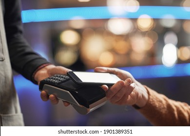 Side view close up of unrecognizable man paying with credit card, focus on hands holding card over terminal, copy space