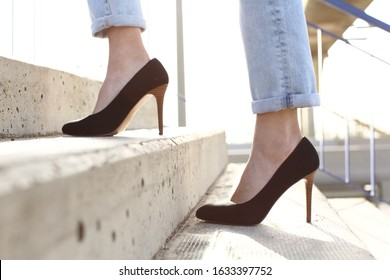 Side view close up of a woman legs wearing high heels walking up stairs