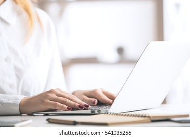 Side view and close up of woman's hands typing on laptop keyboard