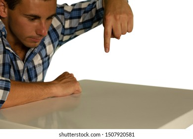 Side view close up of a young Caucasian man wearing a checked shirt sitting at a desk looking down, with one hand held over the desk pointing down or touching