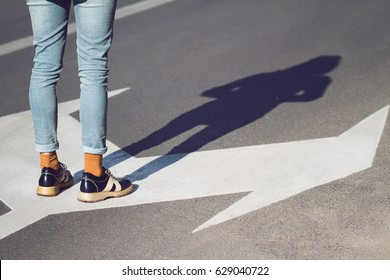 side view close up of a young woman wearing black shoes and blue jeans standing on a street with arrow signs pointing in different directions concept for life choices