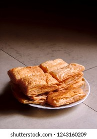 side view of closely packed fresh square shaped puff pastry biscuit snacks on plate placed on diagonal tile background with crispy golden brown crust layers on top visible. Shot in soft natural light